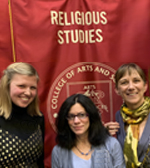 Anna Groover posing in front of Religious studies banner with others