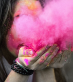 woman blowing pink chalk to make a pink cloud